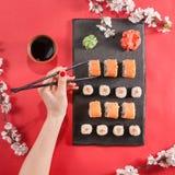 Passi a tenuta i bastoni neri con i sushi sullo scrittorio di cottura scuro Fotografie Stock Libere da Diritti