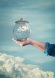 Passi a tenuta il barattolo di vetro con cielo blu e le nuvole dentro Fotografia Stock