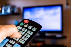 Passi a tenuta il telecomando per cambiare il channesl sulla TV Fotografie Stock