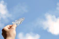 Passi a tenuta l'aereo di carta su un fondo del cielo Immagini Stock Libere da Diritti
