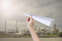 Passi a tenuta l'aereo di carta verso il cielo nuvoloso e la fabbrica Fotografie Stock Libere da Diritti