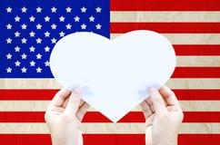 Passi a tenuta la carta bianca del cuore sulla bandiera degli Stati Uniti d'America Fotografia Stock