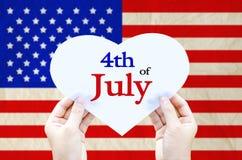 Passi a tenuta la carta bianca del cuore sulla bandiera degli Stati Uniti d'America Fotografie Stock Libere da Diritti