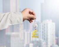 Passi a tenuta la chiave d'argento con l'anello portachiavi dorato di forma di simbolo della libbra, Fotografia Stock