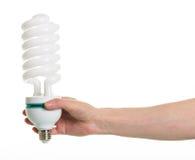 Passi a tenuta la lampada fluorescente a spirale isolata su bianco Fotografia Stock Libera da Diritti