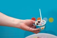 Passi a tenuta la tazza di plastica con il gelato ed il cucchiaio su un fondo blu Immagine Stock