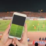 Passi a tenuta lo Smart Phone mobile con lo schermo dello stadio di football americano, bl Immagine Stock