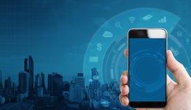 Passi a tenuta lo Smart Phone mobile ed alla tecnologia delle icone dell'applicazione con il fondo della costruzione fotografie stock