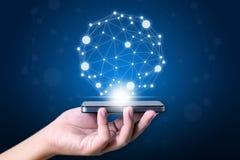 Passi a tenuta lo Smart Phone mobile, il mondo di concetto collegato ed il soc Fotografie Stock