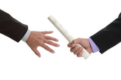 Passing the baton. Partnership or teamwork concept two men handing over a paperwork baton royalty free stock photography
