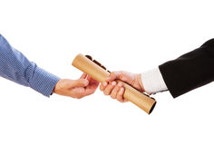 Passing the baton. Close up of two businesspeople holding documents on white background royalty free stock images