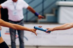 Passing of baton from hand to hand. Women relay race stock photo