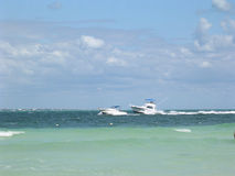 Passing Boats. Two boats, one passing the other with Isla Mujeres on distant horizon.Picture taken fron shoreline in Cancun Mexico Royalty Free Stock Photo