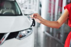 Passing car keys. Cropped closeup of a car dealer holding out car keys to the camera copyspace car dealership salon. Manager salesman selling buying giving stock photo