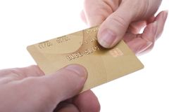 Passing Card. Gold coloured credit card being passed over. Branding, name and number part-removed for security Royalty Free Stock Image