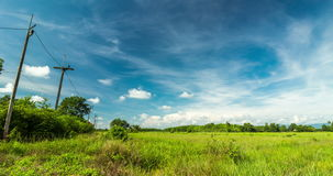 Passing Clouds Over Grassland With Row Of Electric Pole Along The Street stock footage