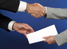 Passing The Envelope. Two people shaking hands and exchanging a white envelope with available copy space for adding text Royalty Free Stock Photo