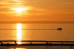 Passing fishing boat at dawn stock image