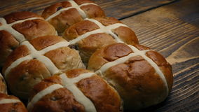 Passing hot cross buns on wooden table stock video