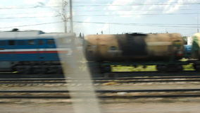 Passing by industrial facility. View from moving train. Passing by industrial facility in countryside with freight trains on platform nearby stock video