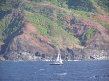 Passing Kauai Island cruising to Big Island Hawaii. A view of Kauai with a sailboat nearby in front on the way cruising to the Big Island of Hawaii Stock Image