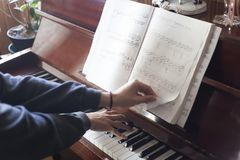 Passing music sheets while playing piano. Hand playing piano while the other changes to the next page of the music sheet to continue playing the piece Stock Photos