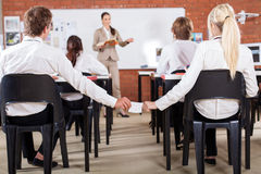 Passing note in classroom Royalty Free Stock Photo