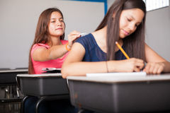 Passing notes in class. Couple of high school teens exchanging notes during class Royalty Free Stock Photography