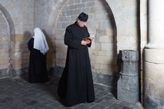 Passing nun and priest. Priest passing a young nun along the walls of a medieval abbey Royalty Free Stock Images