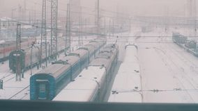 Passing by rail road depo full of trains and hight voltage lines covered in snow. Winter cold blizzard day, slow motion stock footage