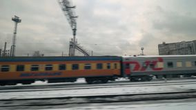 Passing by the railway tracks with trains, Russia. MOSCOW, RUSSIA - DECEMBER 16, 2016: Winter view from the window of train leaving the city. Passing by tracks stock video