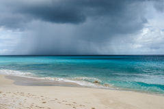 Passing rain cloud and storm over ocean in Anguilla, British West Indies, BWI, Caribbean. Passing storm cloud over ocean from white sand beach in Anguilla island Stock Images
