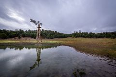 A lone, weathered windmill stands tall. stock photography