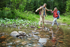Passing river. Adventurous couple crossing river by stepping stones Stock Images