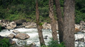 Passing Rocky Jungle River. Moving past a wild jungle river stock footage