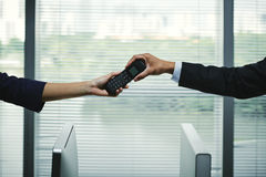 Passing telephone receiver. Hands of businesswoman giving telephone receiver to colleague Royalty Free Stock Photography
