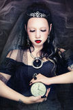 Passing time. Young beautiful gothic woman holding clock in her hands, on vintage grainy damaged background Stock Images