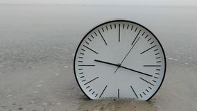 Passing Time Concept Background, Big White Clock on Sand Sea. Passing Time Concept Background, Big White Wall Clock with Black Arrows on Sand Beach of Sea Ocean stock footage