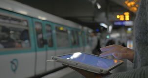 Passing the time with pad in underground. Girl using touch pad at subway station. Defocused arriving train with people getting in and out in the background stock video footage