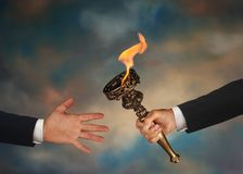 Passing the Torch. Businessman's outstretched arm passing a flaming torch to another businessman's open hand royalty free stock photos