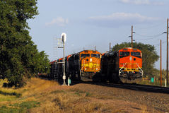 Passing Trains. Two freight trains on a rural stretch of track stock photo