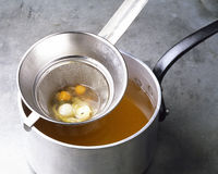 Passing the vegetables through a sieve. Food, gastronomy, cooking,cookery Stock Photo