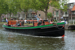 Passing by. River boat passing by on a small city canal in Delft (Netherlands Royalty Free Stock Image
