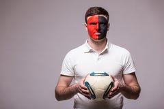 Passioné du football albanais avec la boule dans le jeu de l'équipe nationale de l'Albanie sur le fond gris Photographie stock libre de droits