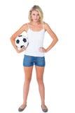 Passioné du football assez blond tenant la boule Image stock
