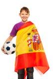 Passioné du football de sourire enveloppé dans le drapeau espagnol Photo stock