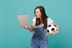Passioné du football embarrassé de jeune femme tenant le ballon de football utilisant l'ordinateur de PC d'ordinateur portable d' photographie stock