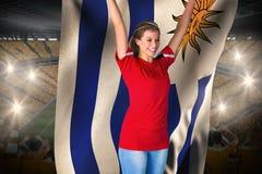 Passioné du football encourageant dans le drapeau se tenant rouge de l'Uruguay Images stock