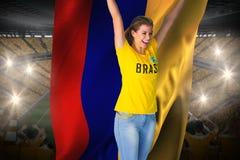 Passioné du football enthousiaste dans le T-shirt du Brésil tenant le drapeau de la Colombie Photographie stock libre de droits