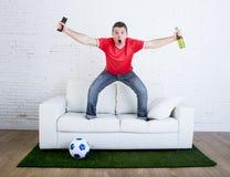 Passioné du football observant le football de TV célébrer le but dans le divan sur le tapis d'herbe émulant le lancement de stade image libre de droits
